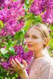 Schöne blonde junge Frau, die zwischen blühendem Fliederbusch steht Stockbilder