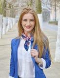 Schöne blonde junge Frau draußen, lächelnd stockfotografie