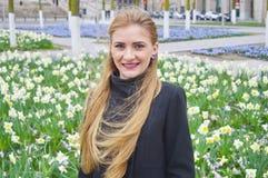 Schöne blonde junge Frau draußen, lächelnd stockfoto