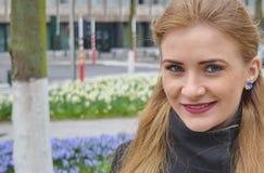 Schöne blonde junge Frau draußen, lächelnd lizenzfreie stockfotografie
