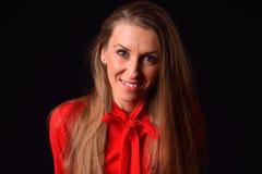 Schöne blonde junge Frau in einem roten Hemd, das in einem Studio O aufwirft Lizenzfreie Stockfotos