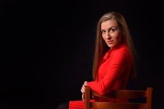 Schöne blonde junge Frau in einem roten Kleid sitzt auf einem Chai Lizenzfreie Stockfotos