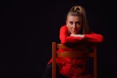Schöne blonde junge Frau in einem roten Kleid sitzt auf einem Chai Stockfotografie