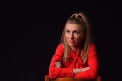 Schöne blonde junge Frau in einem roten Kleid sitzt auf einem Chai Lizenzfreies Stockbild
