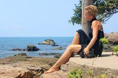 Schöne blonde junge Frau in einem schwarzen Kleid auf dem Strand Stockbild