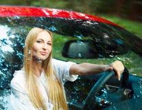 Schöne blonde junge Frau in einem Sportauto Stockfotografie