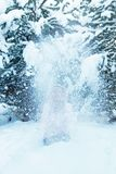 Schöne blonde junge Frau hat Freude und Würfe schneien oben im Winter Stockfotografie