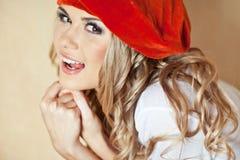 Schöne blonde junge Frau im roten Velourbarett Lizenzfreies Stockfoto