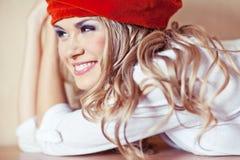Schöne blonde junge Frau im roten Velourbarett Stockfoto
