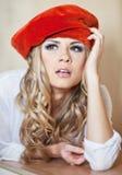 Schöne blonde junge Frau im roten Velourbarett Stockbild