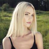 Schöne blonde junge Frau im Wald Stockfotografie