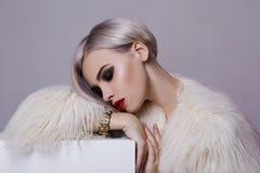 Schöne blonde junge Frau im weißen Pelz Lizenzfreie Stockfotos