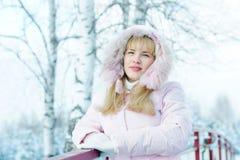 Schöne blonde junge Frau kleidete in der rosa Jacke mit einer Haube an Stockfotografie