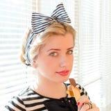Schöne blonde junge Frau mit dem roten Lippenessen Stockfotos