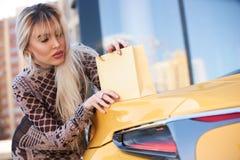 Schöne blonde junge Frau mit Einkaufstasche Stockbild