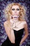 Schöne blonde junge Frau mit purpurrotem Cocktail auf einem Blumenhintergrund Stockfotografie