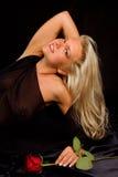 Schöne blonde junge Frau mit Rot stieg Stockfoto