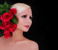 Schöne blonde junge Frau mit roten Rosen über Schwarzem Stockbild