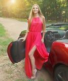 Schöne blonde junge Frau nahe einem Sportauto Stockfoto