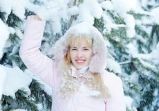 Schöne blonde junge Frau rüttelt Schnee unten von der Niederlassung Lizenzfreie Stockfotografie