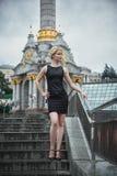 Schöne blonde junge Frau in schwarzes Kleidergehender Dämmerungstreppe draußen in Kyiv Regnerischer Tag Lizenzfreies Stockbild