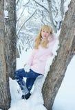 Schöne blonde junge Frau steht zwischen zwei schneebedeckten Bäumen Lizenzfreie Stockbilder