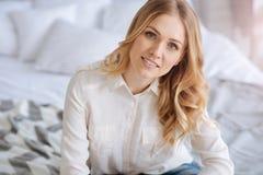 Schöne blonde junge Frau, welche die Kamera betrachtet Lizenzfreie Stockfotos