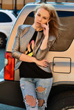 Schöne blonde junge Frau, welche die moderne Kleidung, werfend am Auto trägt auf Lizenzfreies Stockfoto
