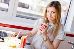 Schöne blonde junge Geschäftsfrau, die ein Cocktail betrachtet die Kamera u. arbeitet an Laptop-Computer trinkt Lizenzfreie Stockfotografie