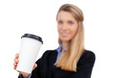Schöne blonde junge Geschäftsfrau, die einen Tasse Kaffee hält Stockbild