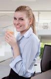Schöne blonde junge Geschäftsfrau im Büro mit Kaffee Lizenzfreies Stockfoto