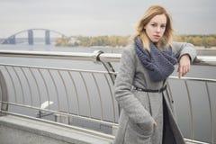 Schöne blonde junge kaukasische Frau in grauem Mantel und Schal wa Stockfotos