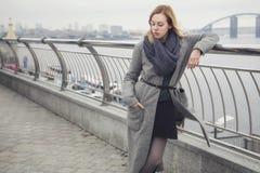 Schöne blonde junge kaukasische Frau in grauem Mantel und Schal wa lizenzfreie stockbilder