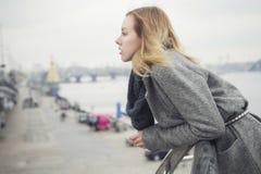 Schöne blonde junge kaukasische Frau in grauem Mantel und Schal wa Lizenzfreie Stockfotos