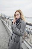 Schöne blonde junge kaukasische Frau in grauem Mantel und Schal wa Stockfotografie