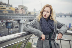 Schöne blonde junge kaukasische Frau in grauem Mantel und Schal wa Stockbild