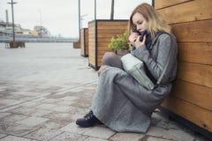 Schöne blonde junge kaukasische Frau in grauem Mantel und Schal wa stockbilder