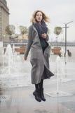 Schöne blonde junge kaukasische Frau in grauem Mantel und Schal wa Lizenzfreies Stockfoto