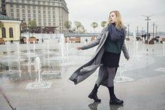 Schöne blonde junge kaukasische Frau in grauem Mantel und Schal wa Lizenzfreies Stockbild
