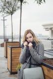 Schöne blonde junge kaukasische Frau in grauem Mantel und Schal wa Stockfoto