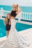 Schöne blonde junge Mutter und die Tochter, gekleidet in Tupfen kleiden an Stockfotografie