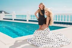 Schöne blonde junge Mutter und die Tochter, gekleidet in Tupfen kleiden an Stockfoto