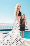 Schöne blonde junge Mutter und die Tochter, gekleidet in Tupfen kleiden an Lizenzfreies Stockfoto