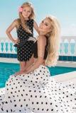 Schöne blonde junge Mutter und die Tochter, gekleidet in Tupfen kleiden an Lizenzfreie Stockfotografie