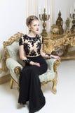 Schöne blonde königliche Frau, die auf ein Retro- Sofa im herrlichen Luxuskleid legt Lizenzfreies Stockbild