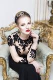 Schöne blonde königliche Frau, die auf ein Retro- Sofa im herrlichen Luxuskleid legt Stockfotos