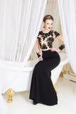 Schöne blonde königliche Frau, die auf einer Badewanne mit Tulle auf ihm im herrlichen Luxuskleid sitzt Stockbild