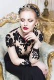 Schöne blonde königliche Frau, die auf einer Badewanne mit Tulle auf ihm im herrlichen Luxuskleid sitzt Lizenzfreies Stockbild