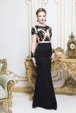 Schöne blonde königliche Frau, die nahe Retro- Tabelle im herrlichen Luxuskleid in camera schaut steht Stockbilder