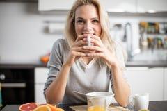 Schöne blonde kaukasische Frau, die in ihrer Küche, beim Trinken in Kaffee oder in Tee und eine gesunde Frühstücksmahlzeit des Ce Stockbilder